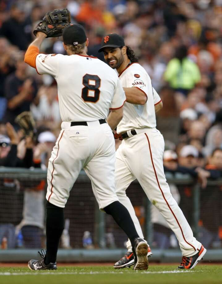 Hunter Pence is either greeting Angel Pagan with a high-five or waving to an adoring fan during a game at AT&T Park. Photo: Scott Strazzante, The Chronicle