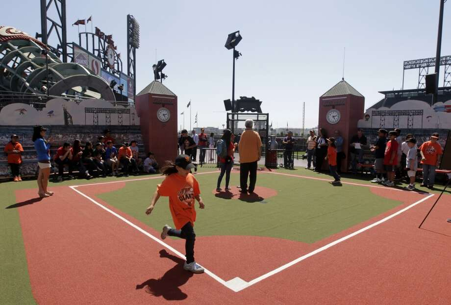 Giants Fan Lot:When the Giants are away, anyone in the community can visit this area of AT&T Park filled with fun activities. Kids will enjoy climbing around a giant baseball glove, whizzing down the Coca-Cola super slide, making funny faces in the photo booth and practicing steals and slides on the mini-size ballpark. Photo: Paul Chinn, The Chronicle