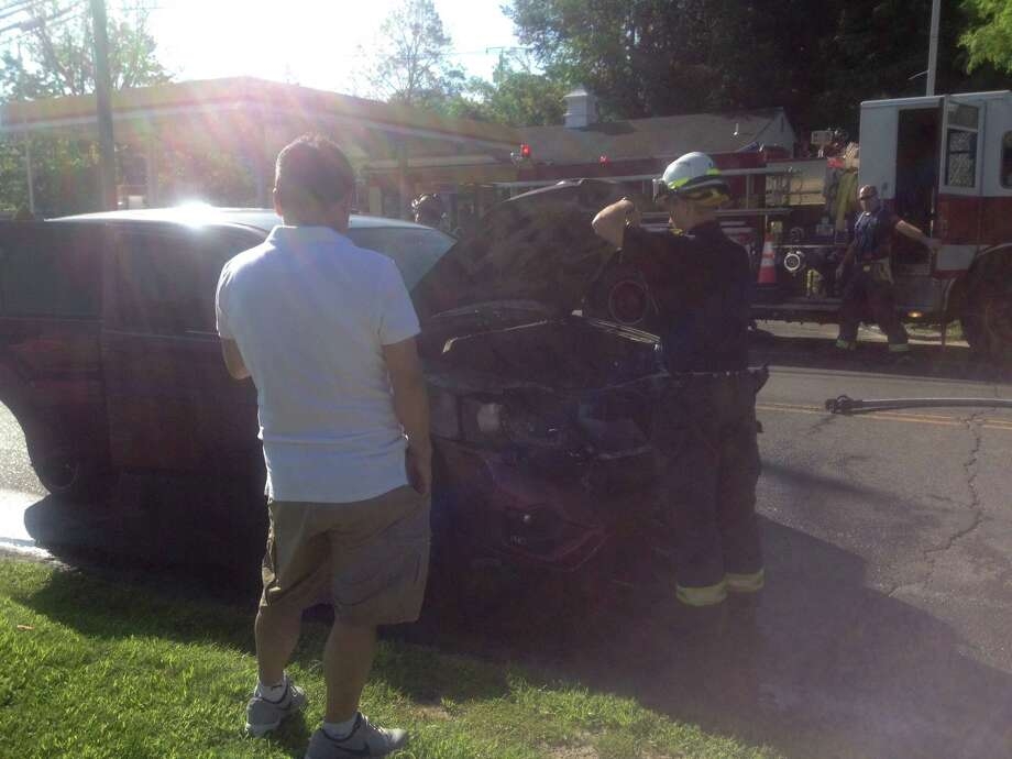 Danbury Deputy Fire Marshal Gary Bruce, and the husband of Lourdes Cardova, the car's owner, inspect her Saturn SUV that burned up Wednesday morning on Newtown Road. Photo: / Susan Tuz, Staff Writer