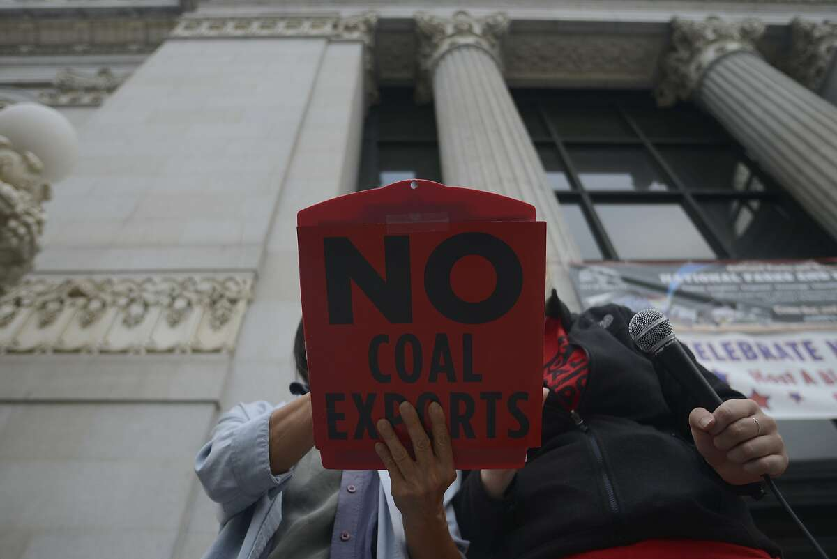 Lora Foo stands infant of Oakland City Hall with her clipboard that speaks out against the plan to build a coal-export facility at the old Oakland Army Base in Oakland, California, on Tuesday, July 21, 2015.
