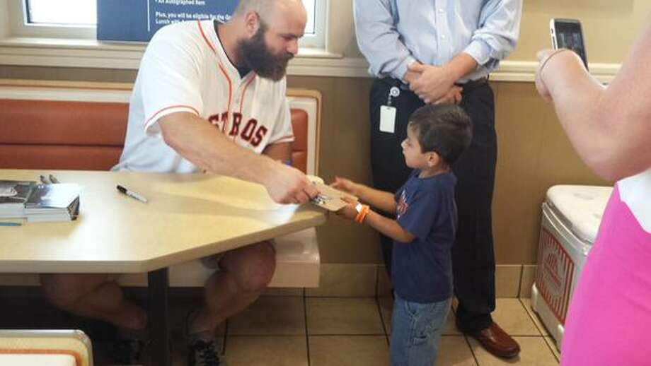 Astros slugger Evan Gattis interacts with a young fan Tuesday at a Whataburger appearance in Baytown. Photo: Brian T. Smith/Houston Chronicle