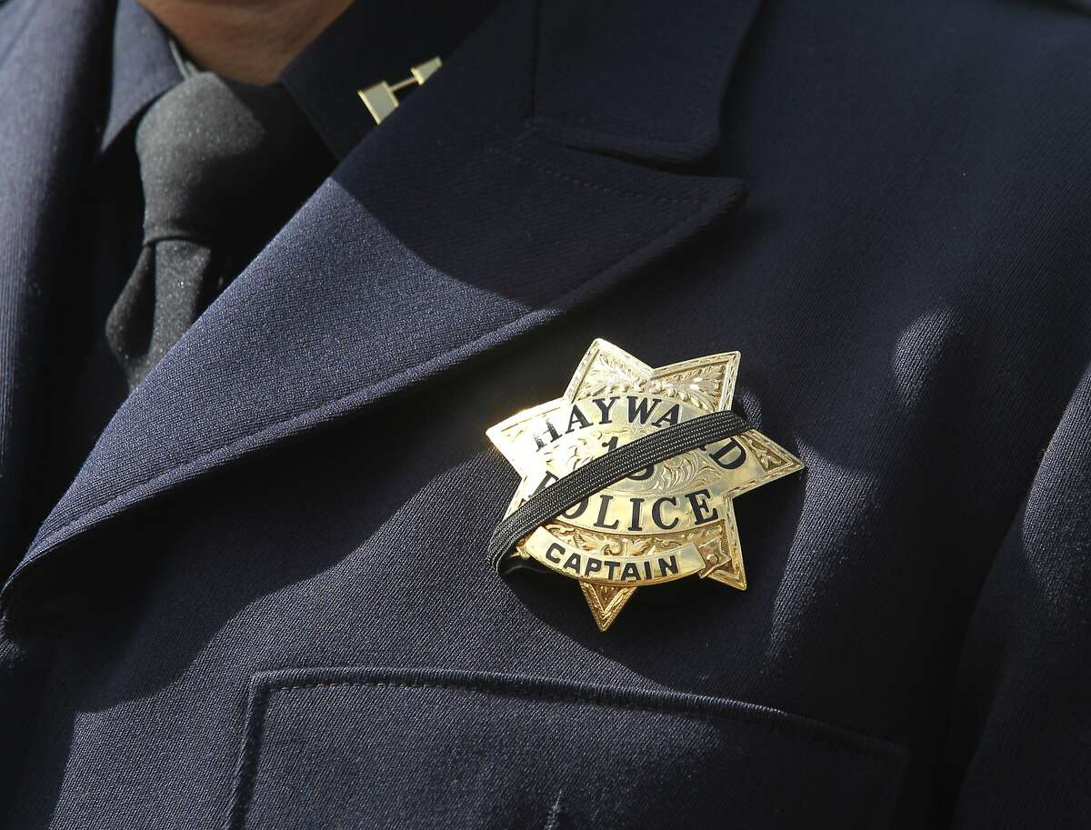 A black memorial stripe covers Capt. Mark Koller's badge while he announces the death of Hayward Police Sgt. Scott Lunger, who was shot and killed during a routine traffic stop earlier this morning, during a news conference at City Hall in Hayward, Calif. on Wednesday, July 22, 2015.