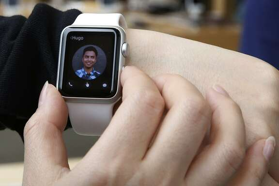 FILE - In this April 10, 2015, file photo, a customer tries on an Apple Watch at an Apple Store in Hong Kong. Although very few are dismissing the Apple Watch as a bomb, the mixed reviews underscore that Apple still has a lot of work to do in showing how the watch might fit in with everyday life. (AP Photo/Kin Cheung, File)
