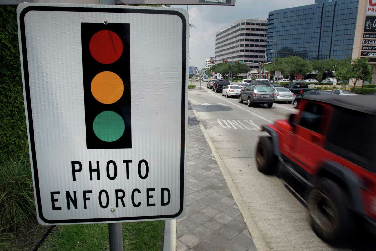FILE - An undated photograph of signage indicating an upcoming street light features a red-light camera. A Sugar Land resident has filed a lawsuit over their use in the city.
