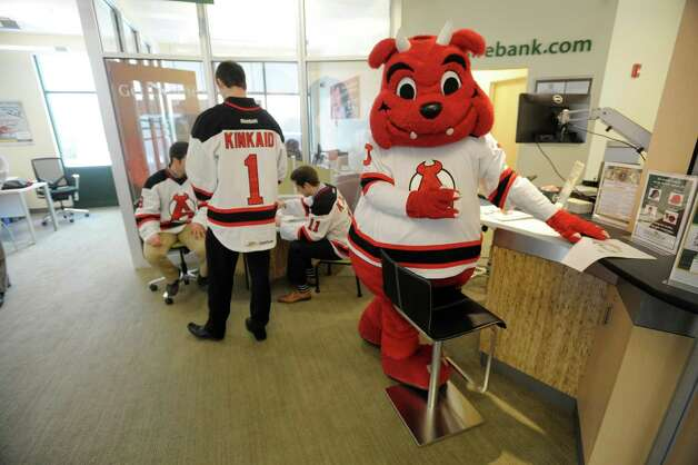 Albany Devils mascot, Devil Dawg along with players, Joe Whitney, left, Keith Kinkaid, center, and Kelly Zajac take part in a grand opening celebration at a Berkshire Bank on Wednesday, Feb. 20, 2014 in Loudonville, NY.  This branch incorporates the bank's new teller pods which banking officials say allows for a more personal and friendly interaction with their customers.  The grand opening celebration will continue with a ribbon cutting ceremony and reception on Wednesday, February 26th at 11:00am.   (Paul Buckowski / Times Union) Photo: Paul Buckowski / 00025755A