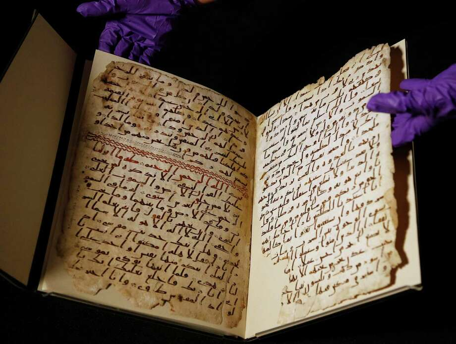 A university assistant shows fragments of an old Quran at the University in Birmingham, in central England. The university said scientific tests prove a Quran manuscript in its collection is one of the oldest known and might have been written within a few years of Islam's founding. Photo: Frank Augstein /Associated Press / AP