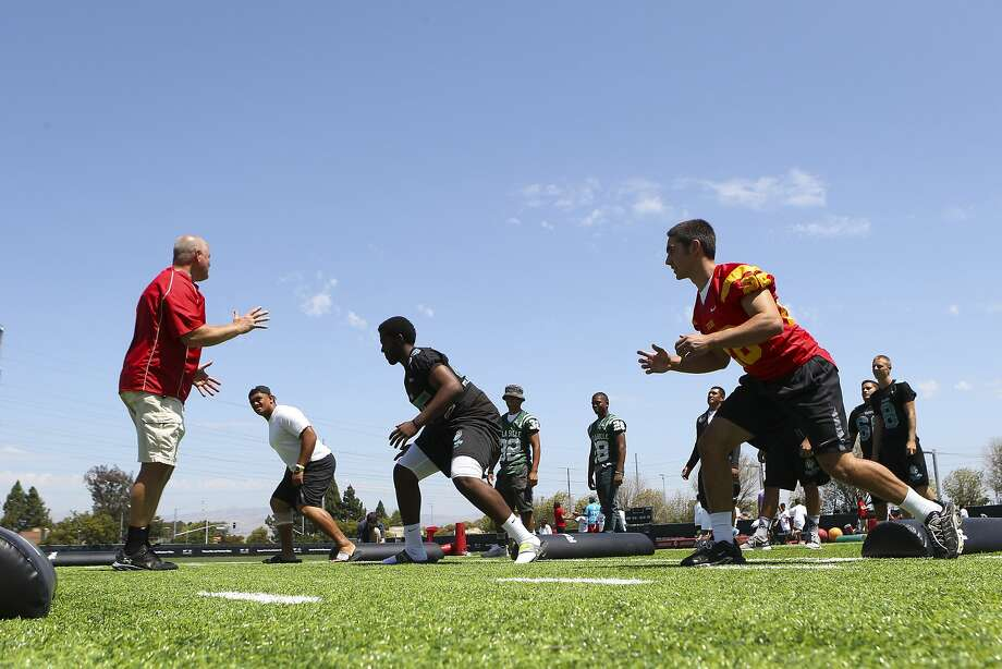 """From left: Terry Summerfield, regional master trainer for USA Football's """"Heads Up Football"""" program, runs a drill with De La Salle's Boss Tagaloa, Deer Valley's Troy Decuir and Jesuit's Theo Christopulos during High School Football Media Day at Levi's Stadium in Santa Clara, CA, on Wednesday, July 22, 2015. The event was hosted by the San Francisco 49ers, USA Football and MaxPreps. USA Football's Heads Up Football program is a national initiative to make the sport safer. Photo: Loren Elliott, The Chronicle"""