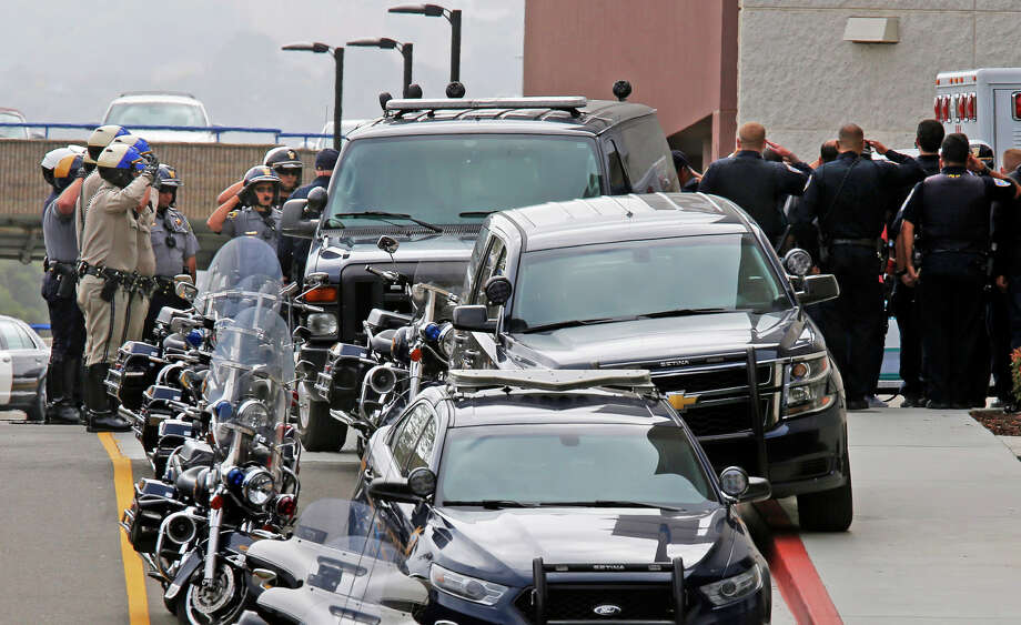 Law enforcement officers salute as the body of Hayward police Sgt. Scott Lunger leaves Eden Medical Center in Castro Valley. Photo: Michael Macor / Michael Macor / The Chronicle / ONLINE_YES