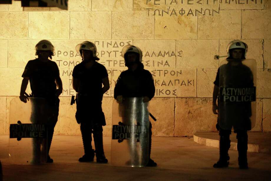 Riot police stand guard in front of the Tomb of the Unknown Solider outside the Greek parliament during a demonstration by anti-bailout protesters in central Athens, Greece. Photo: Matthew Lloyd / © 2015 Bloomberg Finance LP