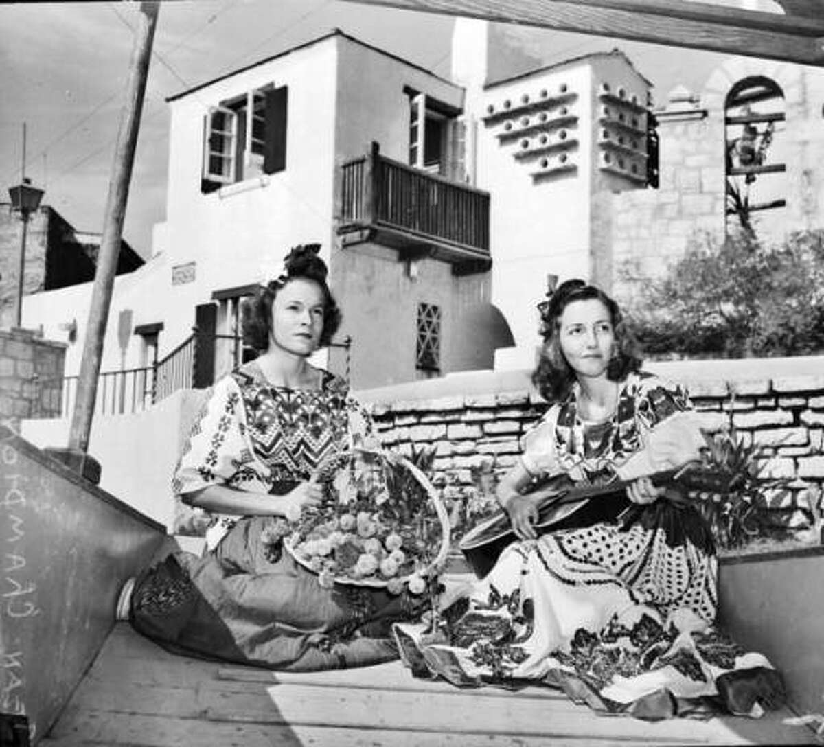 Jean Champion, with guitar, and Joan Brown, both in costume, pose in a sight-seeing gondola as it passes the Arneson River Theatre in 1942.