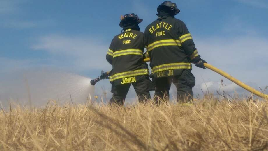 Firefighters demonstrate how they tackle a brush fire Wednesday at Discovery Park. The demonstration served as a reminder for Seattle residents to help prevent brush fires, as the city has already seen more than double the brush fires as there were all of last year.