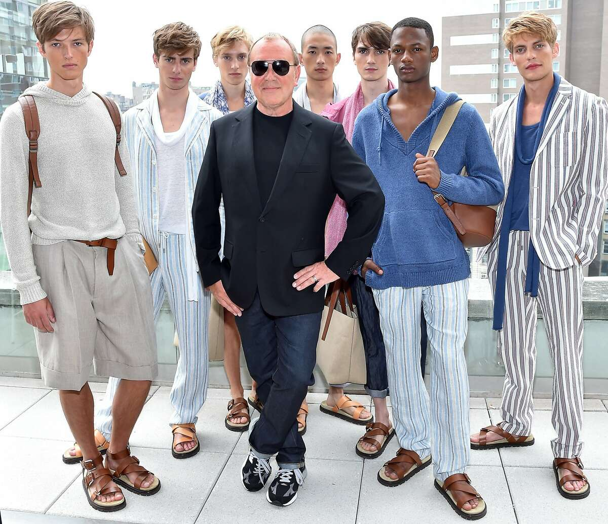 NEW YORK, NY - JULY 15: (EDITORS NOTE: Retransmission of image 480764150 with alternate crop.) Designer Michael Kors (C) and models pose at the Michael Kors Spring 2016 Presentation during New York Fashion Week: Men's at Spring Studios on July 15, 2015 in New York City. (Photo by Larry Busacca/Getty Images for Michael Kors)