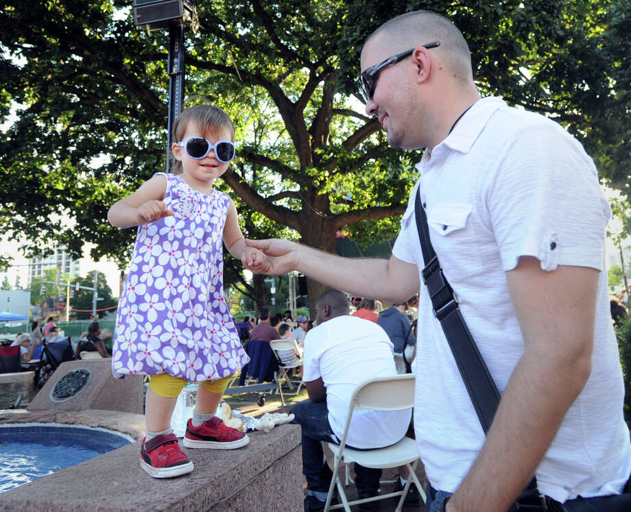 At right, Mike Wiston of Stamford holds the hand of his daughter, Natalie, 2, as the pair danced to Joe Benjamin and a Mighty Handful as they performed as part of Jazz-Up-July concert series in Columbus Park, Stamford, Conn., Wednesday evening, July 22, 2015. Photo: Bob Luckey Jr. / Hearst Connecticut Media / Greenwich Time