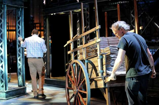 "Tour prop worker Dan Boesch, right, moves a cart filled with newspapers onto the set of ""Newsies"" on Wednesday, Oct. 1, 2014, at Proctors Theatre in Schenectady, N.Y. (Cindy Schultz / Times Union) ORG XMIT: MER2014100115320710 Photo: Cindy Schultz / 00028846A"