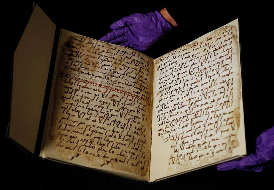 A university assistant shows fragments of an old Quran at the University in Birmingham, in Birmingham central England Wednesday, July 22, 2015. The University of Birmingham said Wednesday that scientific tests prove a Quran manuscript in its collection is one of the oldest known and may have been written close to the time of the Prophet Muhammad. Radiocarbon testing at Oxford University dated the parchment to the time of the prophet, who is generally believed to have lived between 570 and 632.(AP Photo/Frank Augstein) ORG XMIT: FAS104 Photo: Frank Augstein / AP