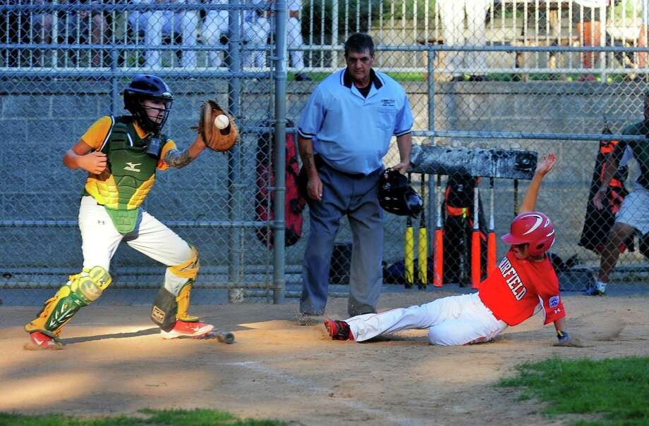 Fairfield American's Kyle Stevenson slides safely into home as Hamden catcher Alex Ponzio receives the ball Wednesday at McGuane Park in Darien. Photo: Christian Abraham / Hearst Connecticut Media / Connecticut Post
