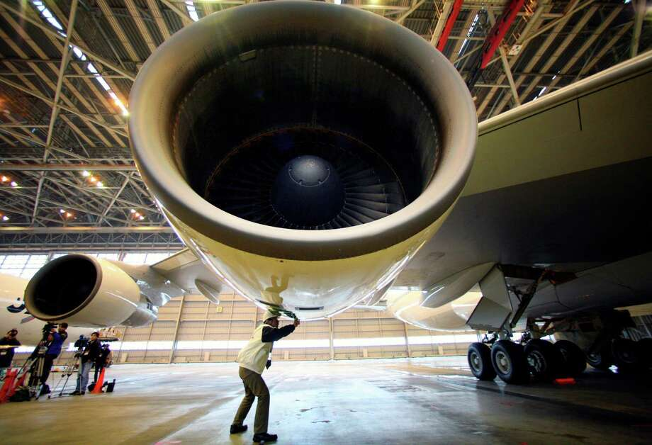 A Japan Air Lines staffer checks the biofuel-loaded No. 3 engine of Japan Airlines Boeing 747-300 before a flight at Tokyo International Airport in Tokyo. The industry is expected to turn to biofuels as world travel grows. Photo: Itsuo Inouye /Associated Press / AP