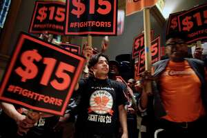 FILE - In this June 15, 2015, file photo, demonstrators rally for a $15 minimum wage before a meeting of the state Wage Board in New York. The New York state Wage Board is expected to recommend a higher minimum wage for the industry during a meeting Wednesday, July 22, 2015, in New York City. Board members say they support an increase, though they haven't offered a specific amount. (AP Photo/Seth Wenig, File)