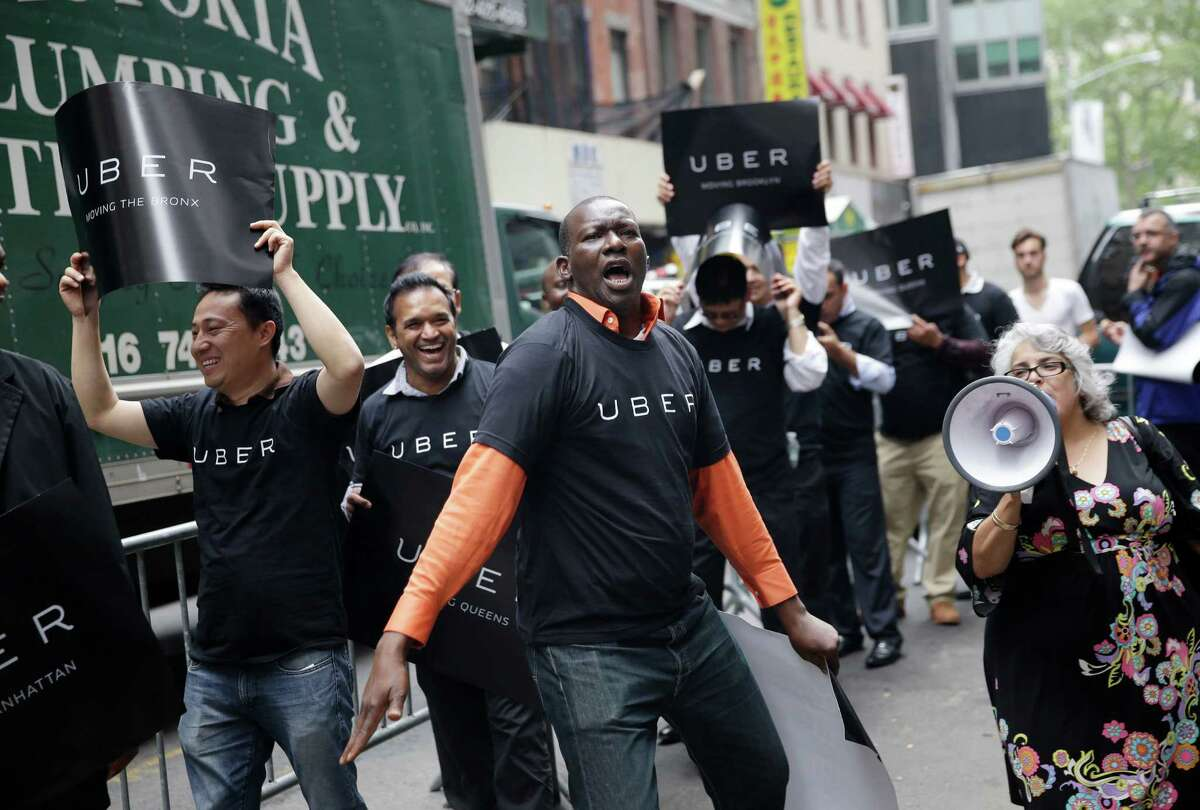 Uber drivers and their supporters protest in front of the offices of the Taxi and Limousine Commission in New York on May 28, where a proposal before the commission would require car services that riders can summon with their phones to comply with many of the rules that govern the yellow cabs they compete with. (AP Photo/Seth Wenig)