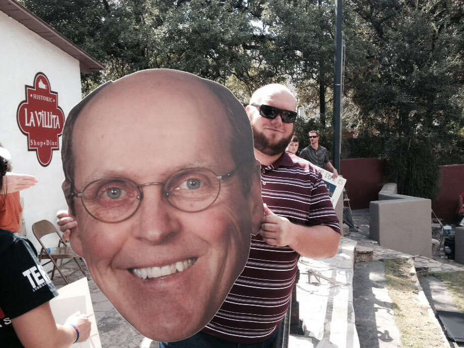A fan holds a giant cutout of Bill Hancock, executive director of the College Football Playoff, at a rally at the Arneson River Theatre in La Villita in San Antonio. Hancock was in town visiting with city and Alamo Bowl officials about the prospects of the city hosting a future playoff game. Photo: Tim Griffin / San Antonio Express-News, Tim Griffin / San Antonio Express-News