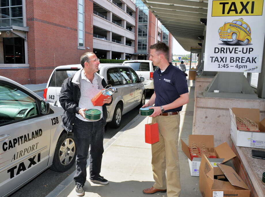 Capitaland Airport Taxi driver Ford McLain, left, of Albany receives a a free gift bag with snacks and tokens of appreciation from Schuyler Bull of the Albany County Convention & Visitors Bureau during their 5th Taxi Day at Albany International Airport Thursday May 8, 2014, in Colonie, NY.  (John Carl D'Annibale / Times Union) Photo: John Carl D'Annibale / 00026814A