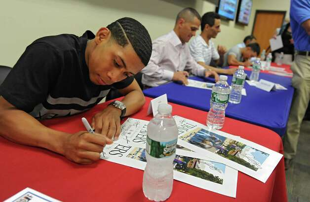 Jockey Manuel Franco signs a Greg Mongomery Travers poster for a fan as jockeys sign memorabilia for a donation of $10 at the Clubhouse Race Book on Wednesday, July 22, 2015 in Albany, N.Y. All proceeds go to the PDJF.  (Lori Van Buren / Times Union) Photo: Lori Van Buren / 00032697A