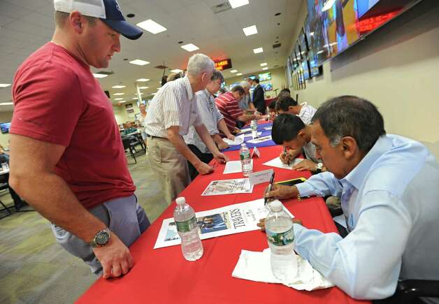 Brian Carr of Albany, left, gets a Greg Montgomery Travers poster signed by Angel Cordero, Jr. as jockeys sign memorabilia for a donation of $10 at the Clubhouse Race Book on Wednesday, July 22, 2015 in Albany, N.Y. All proceeds go to the PDJF.  (Lori Van Buren / Times Union) Photo: Lori Van Buren / 00032697A