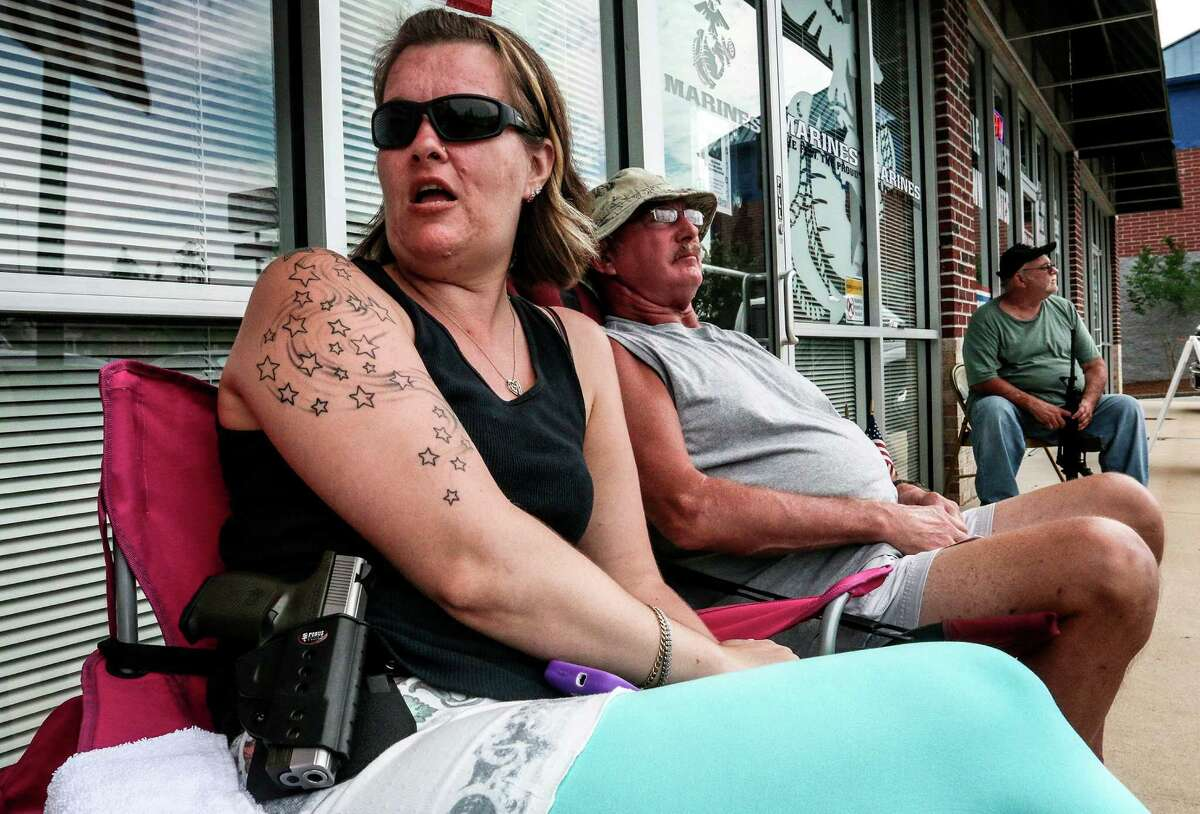 Crystal Tewelow, armed with a loaded gun on her hip, talks with fellow gun owners in front of an Army and Marine recruitment center on Wednesday, July 22, 2015, in Hiram, Ga. Tewelow was one of several armed citizens who held watch at the recruitment center in response to the deadly shooting at a similar facility in Chattanooga, Tenn. (AP Photo/Ron Harris) ORG XMIT: GARH103