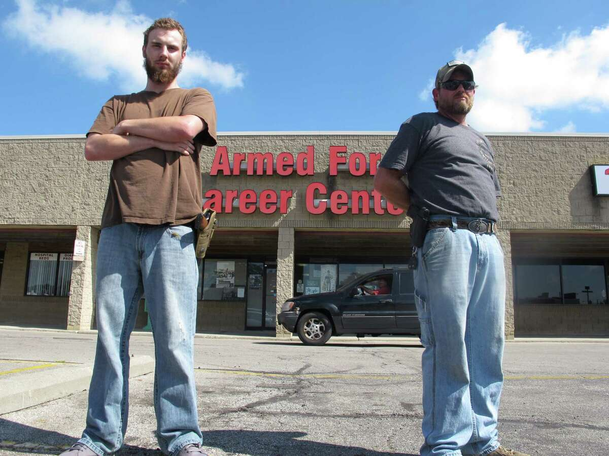In this photo taken Tuesday, July 21, 2015, Allen Bowles, left, and Clint Janney stand guard outside a military recruiting center in Columbus, Ohio. The men are members of the 3 Percent Irregulars Militia, and say they plan to protect the center until the government provides its own security.(AP Photo/Andrew Welsh-Huggins) ORG XMIT: OHAW101