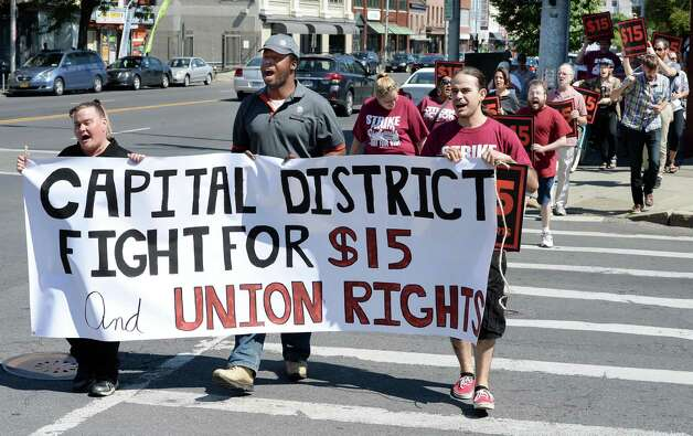 Fast food workers, from left, Stacey Ellis of Schenectady, Trivell Caruth of Albany and Peter Rodriguez of Troy, carry a banner as demonstrators march along Central Avenue in reaction to the upstate conditions of Gov. Cuomo's The Fast Food Wage Board recommendations during a viewing party at the Citizen Action offices Wednesday July 22, 2015 in Albany, NY.   (John Carl D'Annibale / Times Union) Photo: John Carl D'Annibale / 00032696A