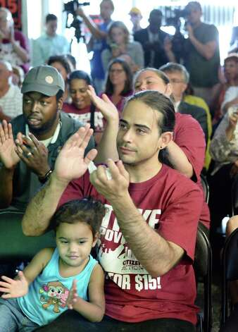 Peter Rodriguez of Troy and his daughter Ziana, 2, applaud Gov. Cuomo's The Fast Food Wage Board recommendations to increase minimum wages during a viewing party at the Citizen Action offices Wednesday July 22, 2015 in Albany, NY.   (John Carl D'Annibale / Times Union) Photo: John Carl D'Annibale / 00032696A