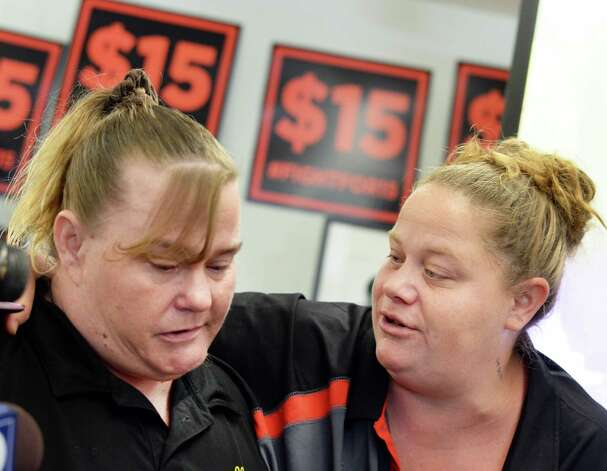 McDonalds worker Stacey Ellis, left, of Schenectady is comforted by fellow McDonalds worker Amanda Monroe of Colonie after learning of upstate conditions imposed by The Fast Food Wage Board during a viewing party at the Citizen Action offices Wednesday July 22, 2015 in Albany, NY.   (John Carl D'Annibale / Times Union) Photo: John Carl D'Annibale / 00032696A