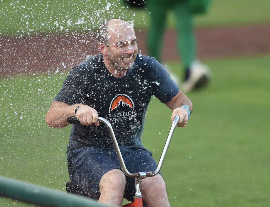 Ben Liebermann, a contestant in a tricycle race, receives a cooling shower from the visiting dugout at Wolff Stadium on Wednesday, July 22, 2015. Photo: Billy Calzada, Staff / San Antonio Express-News / San Antonio Express-News