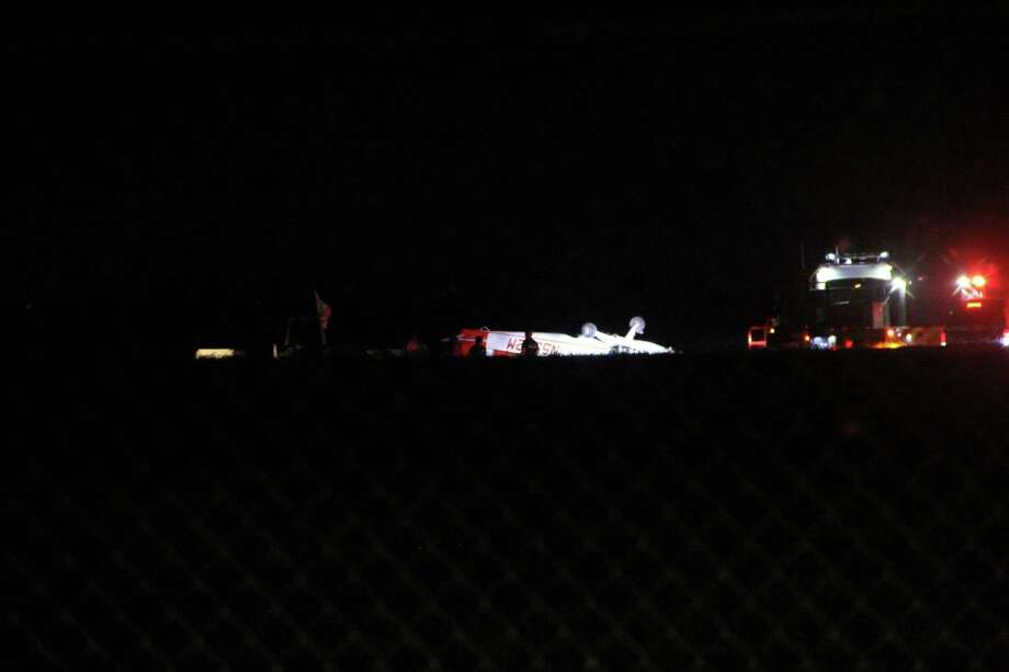 San Antonio Fire Department crews examine the wreckage of a fixed wing single-engine aircraft after an accident Wednesday night, July 22, at Stinson Municipal Airport in the 8500 block of Mission Road. Photo: Jacob Beltran