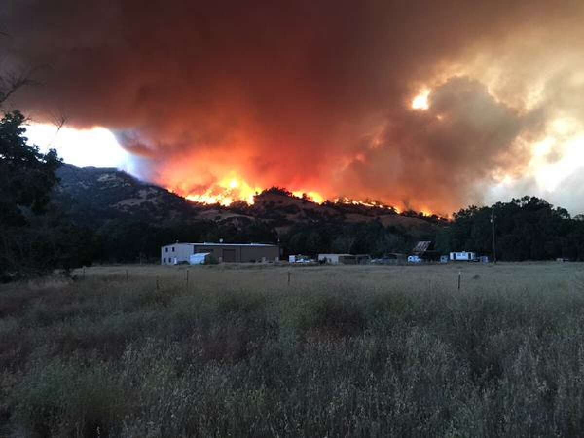 The Wragg Fire spreads near homes on Quail Canyon Road in Vacaville on July 22, 2015.