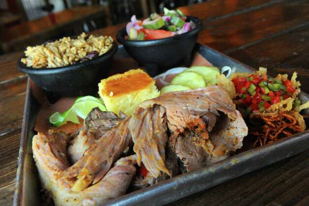 House special smoked brisket with sides of dirty rice and tomato and cucumber salad at The Barrel Saloon at 942 Broadway on Thursday July 16, 2015 in Albany, N.Y. (Michael P. Farrell/Times Union) Photo: Michael P. Farrell / 00032623A