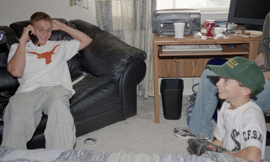 Scott Kazmir, who went 15th in the first-round draft to the Mets, talks to the Mets on the phone, as his former bat boy for his Cy Falls high school team, R.J. Powell, 8,  listens to the conversation in Kazmir's home Tuesday afternoon.  (Karen Warren/Houston Chronicle). Photo: Karen Warren, Houston Chronicle