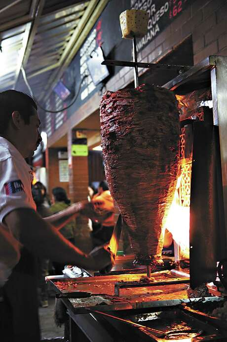Tacos al pastor meat on a vertical spit at a market in Mexico City. Photo: Penny De Los Santos /Courtesy Kyle Books