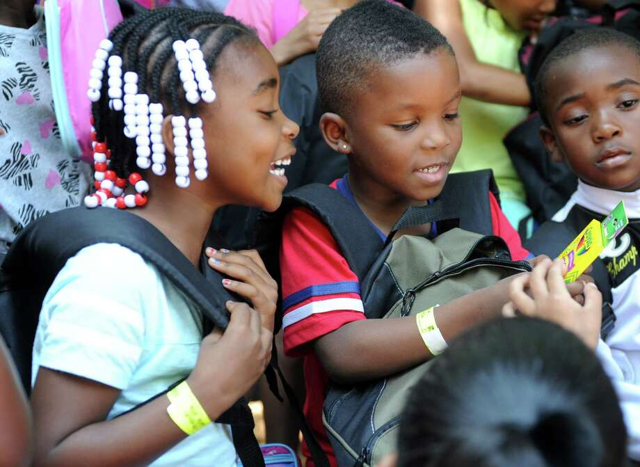 Hallen Elementary School kindergarten students Jamaya Irby and Travis Dyer check out the back-to-school supplies in their new backpacks Thursday, July 16, 2015, at Connecticut's Beardsley Zoo in Bridgeport, Conn. Photo: Autumn Driscoll / Hearst Connecticut Media / Connecticut Post