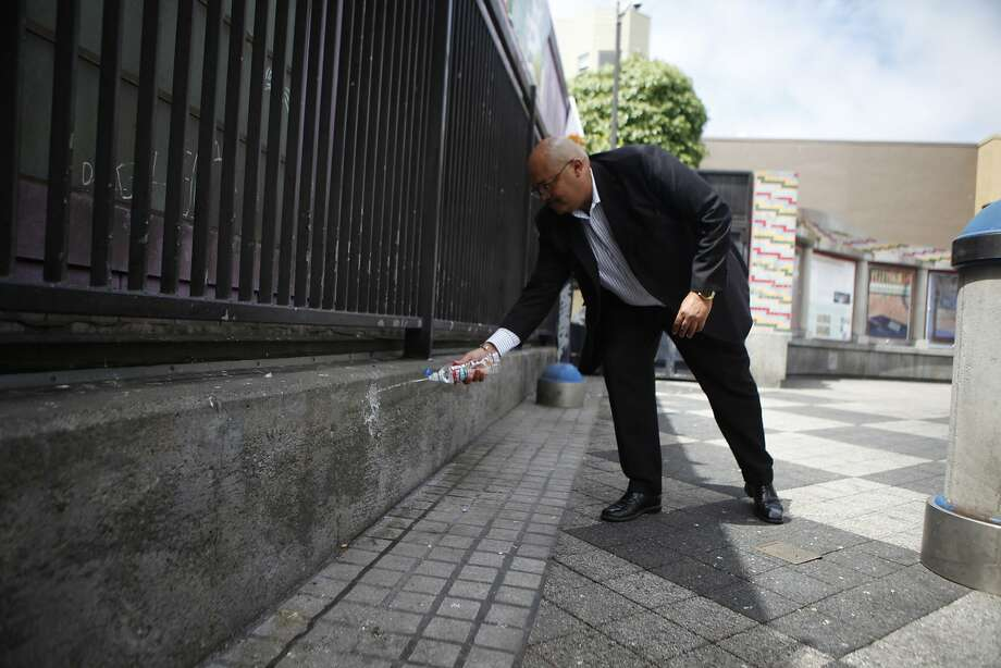 Using the wall at 16th Street and Mission as an example, Public Works director Mohammed Nuru demonstrates how the walls deflect liquid onto the clothes of those that urinate on the walls. Photo: Cameron Robert, The Chronicle