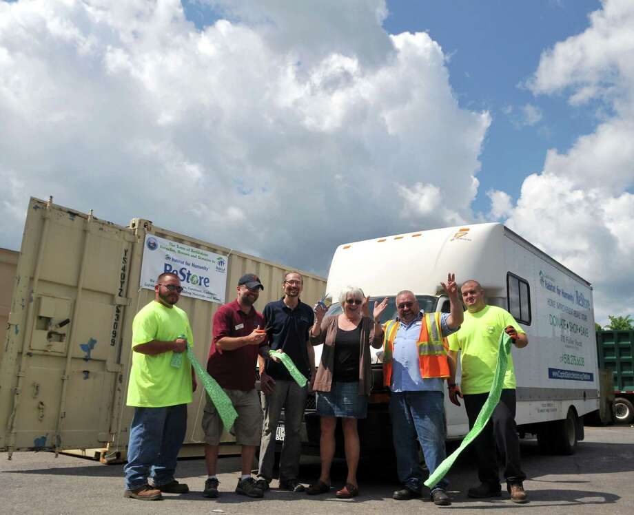 From left, transfer station attendant Sean Dwyer Jr., ReStore manager Dave Harrison, recycling coordinator Dan Rain, Town Clerk Nanci Moquin, equipment operator Mike Gervais and transfer station attendant Devin Clark  cut the ribbon during a ceremony for a new Habitat for Humanity donation program Thursday, July 23, 2015, at the Town of Bethlehem Transfer Station in Selkirk, N.Y. (Phoebe Sheehan/Special to The Times Union) Photo: PS / 00032719A