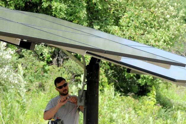 Kevin Bailey of High Peaks Solar installs solar panels at a home on Friday July 17, 2015 in East Greenbush, N.Y. (Michael P. Farrell/Times Union) Photo: Michael P. Farrell / 00032652A