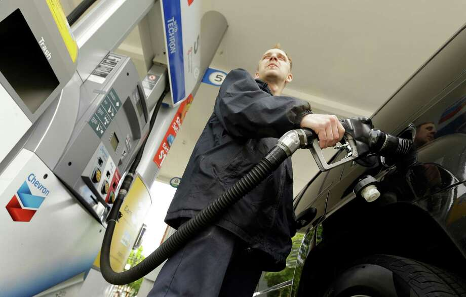 In this May 6, 2015 photo, attendant James Lewis pumps gas at a station in Portland, Ore. Even after the typical springtime run-up, the average price for gallon of regular gasoline should top out around $2.60, experts say. (AP Photo/Don Ryan) Photo: Don Ryan, STF / AP