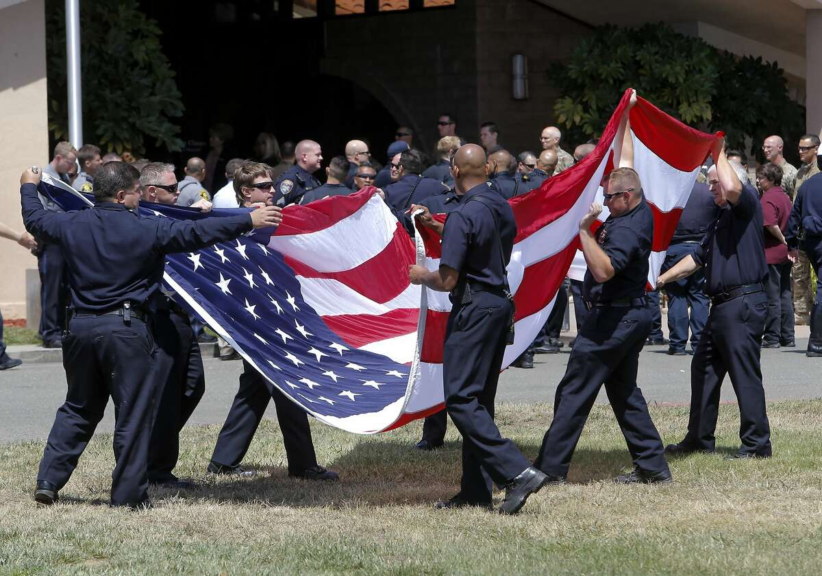Hayward firefighters retire the colors after a police escort brought the body of slain Hayward Police Sgt. Scott Lunger to the Chapel of the Chimes funeral home in Hayward, Calif. on Thurs. July 24, 2015.
