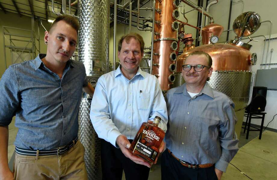 Yankee Distllery's partners, Matthew Jager, left, Walter Kleemeier, center, and Scott Luning hold their bourbon at the distllery's grand opening Thursday afternoon, July 23, 2015, in Clifton Park, N.Y.  (Skip Dickstein/Times Union) Photo: SKIP DICKSTEIN / 00032589A