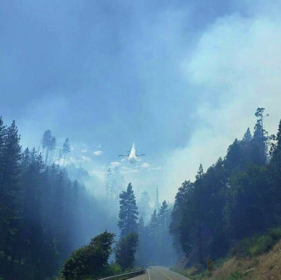 A plane fights the Kyburz Fire the afternoon of Thursday, July 23, 2015. The blaze closed Highway 50 in the Sierra. Photo: @shania_pence, Twitter