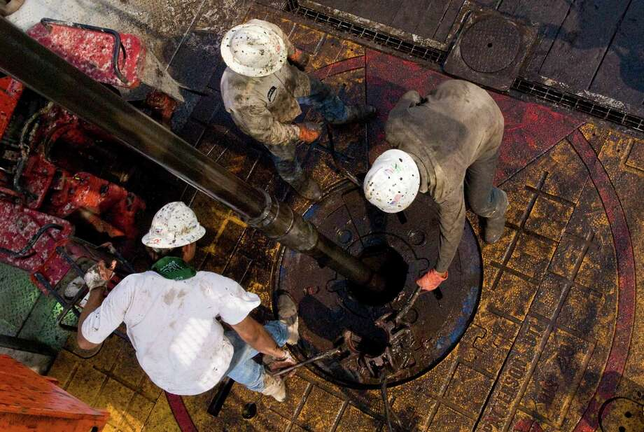 Patterson UTI Drilling Co. floorhands move a drill pipe collar as pipe is removed from a well being drilled in the Eagle Ford Shale in Karnes County. Houston-based Patterson-UTI lost $19 million in the second quarter as oil companies sidelined hundreds of drilling rigs. Photo: Eddie Seal /Bloomberg News / © 2010 Bloomberg Finance LP