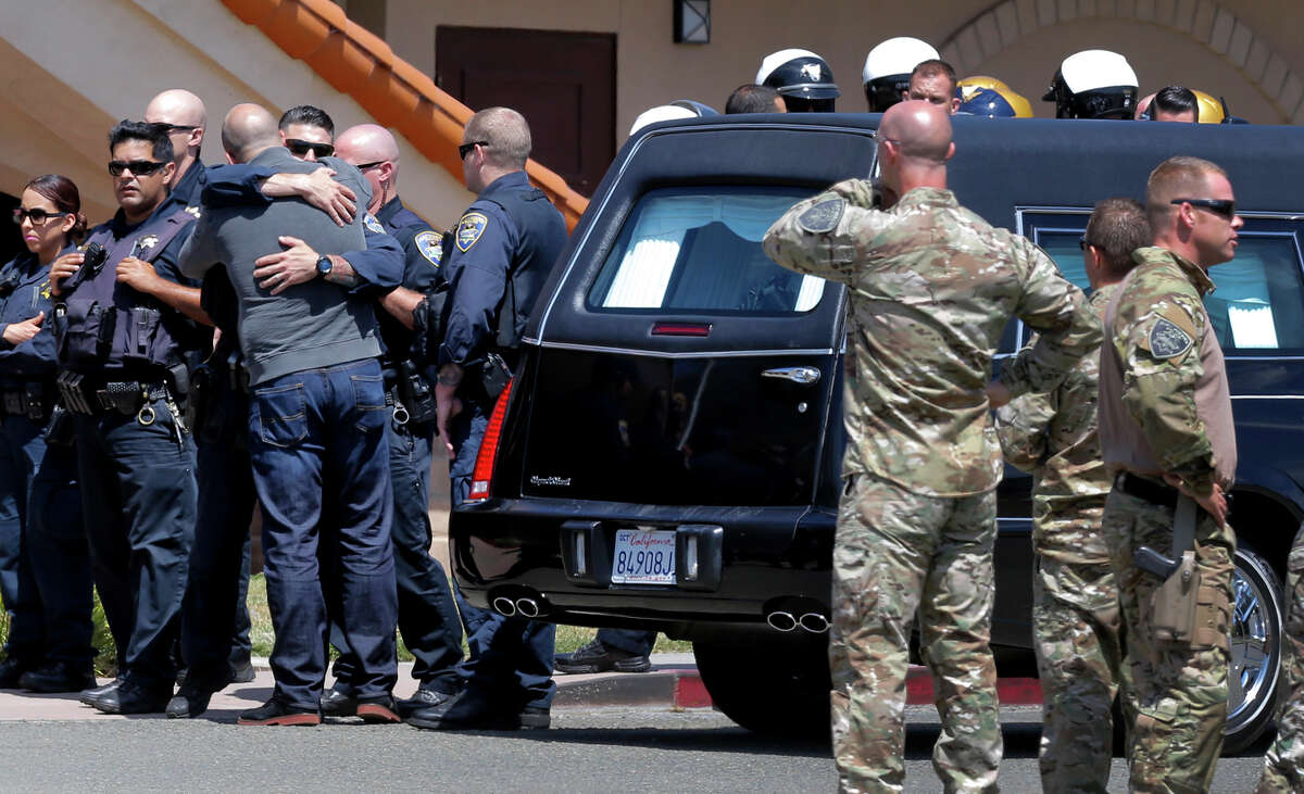 Police personnel surround a hearse carrying the body of Sgt. Scott Lunger to a Hayward funeral home.