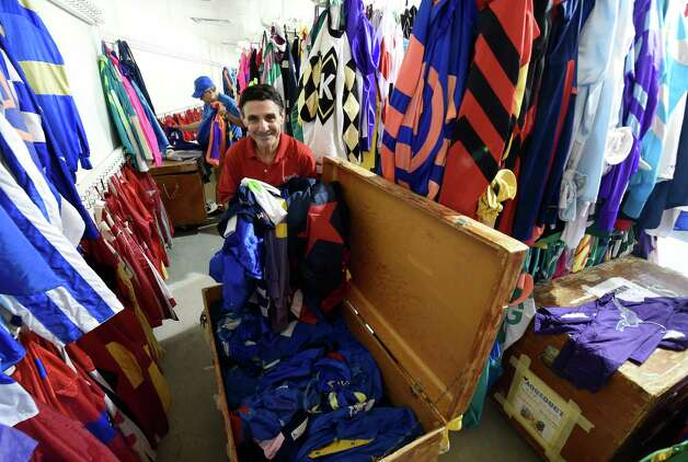 Frankie Lopez, foreground, and Walter Arce put out some of the hundreds of silks in the Silks Room Thursday, July 23, 2015, at the Saratoga Race Course in Saratoga Springs, N.Y. The historic track opens Friday.  (Skip Dickstein/Times Union) Photo: SKIP DICKSTEIN / 00032589A