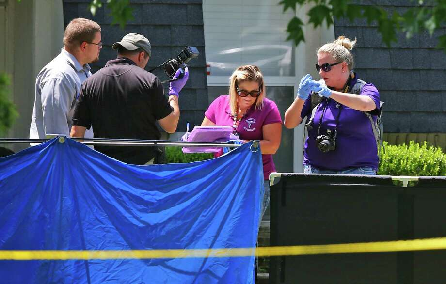 Investigators look down at a body outside a home in Broken Arrow, Okla. Police responding to a 911 call found the bodies of two boys, a girl and their parents. Two other daughters survived. Photo: Sue Ogrocki /Associated Press / AP